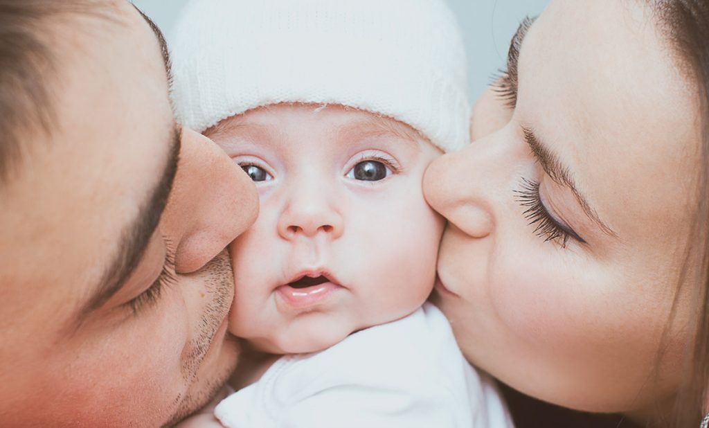 Parents kissing baby - Natalis make a positive difference for you & your baby